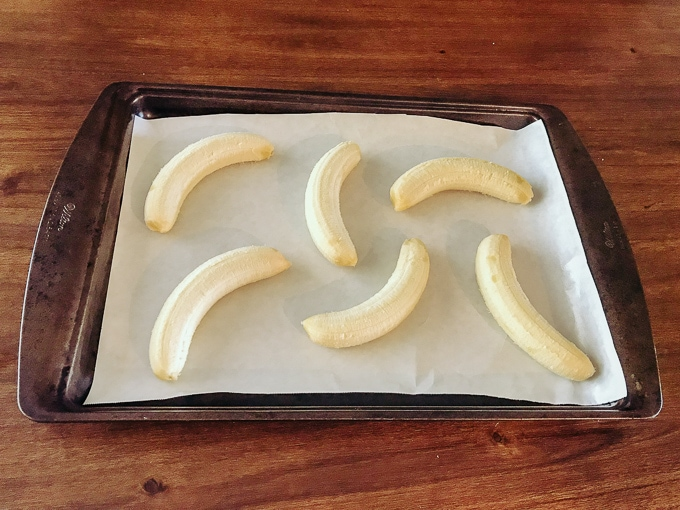 Six peeled bananas on a cookie sheet.