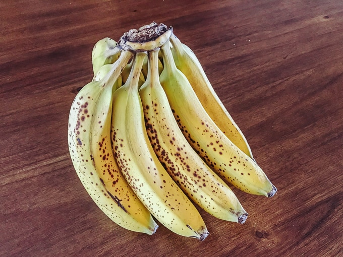 A picture of a bunch of bananas on a wooden table.