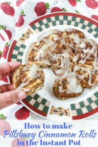 """A hand pulling a cinnamon roll from a batch of rolls with the words """"how to make pillsbury cinnamon rolls in the instant pot""""."""