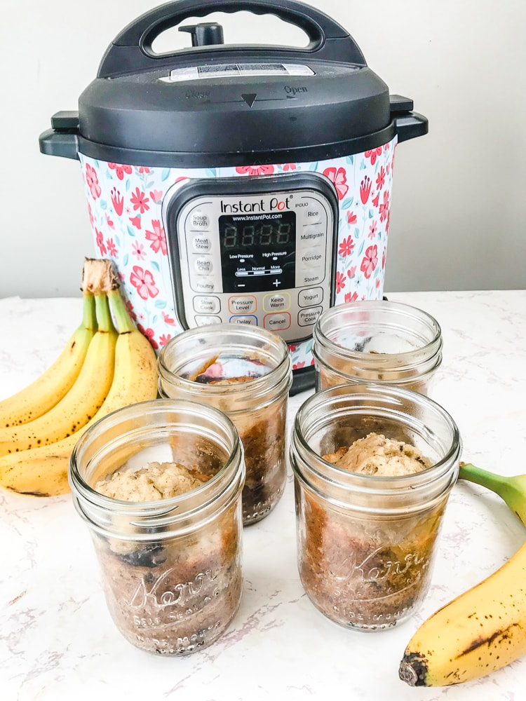 Four jars of banana bread next to a bunch of bananas and an instant pot.