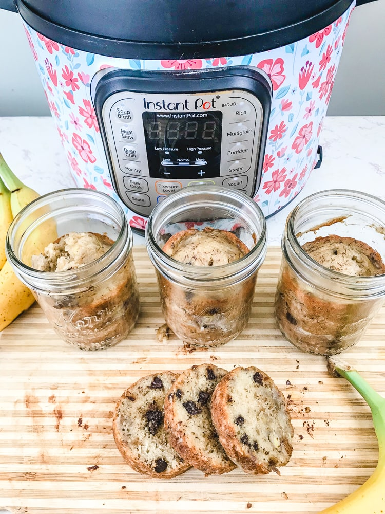 Three jars of instant pot banana bread in jars behind a loaf of banana bread cut into round slices.