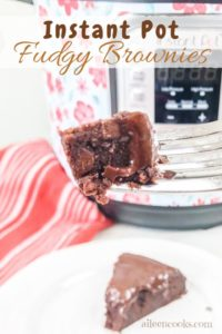 A bite of instant pot brownies from scratch held up in front of an instant pot.