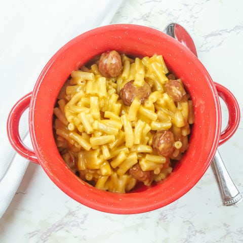 Overhead shot of red bowl of instant pot Kraft Mac and cheese with hot dogs.