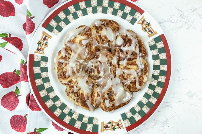 A red and green fall-themed plate topped with instant pot pillsbury cinnamon rolls.