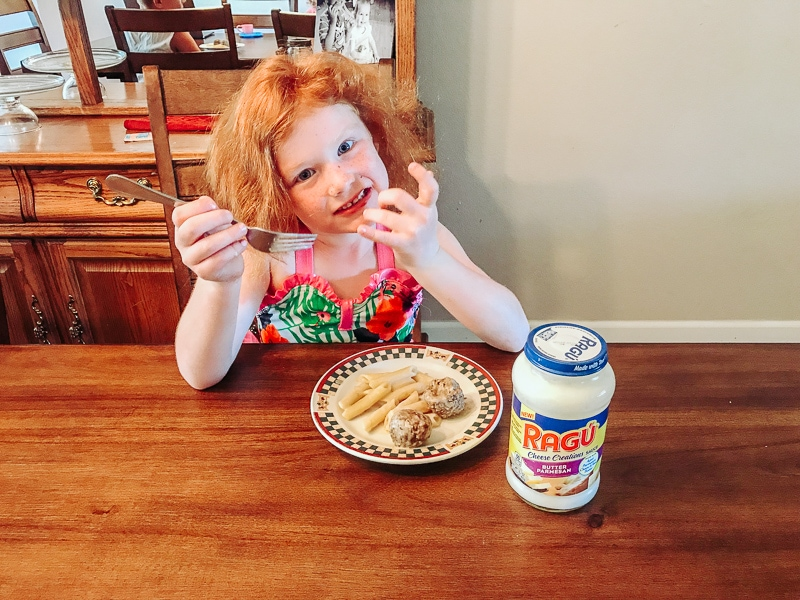 A girl eating pasta made with Ragu Butter sauce.