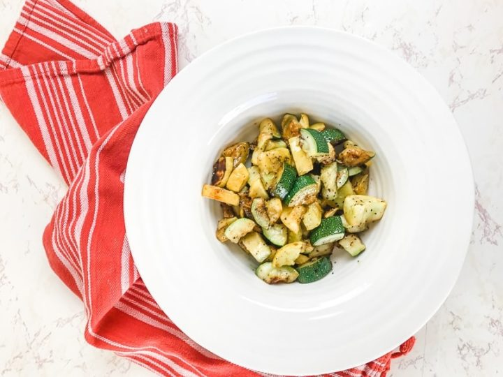 A white bowl filled with roasted zucchini and yellow squash.