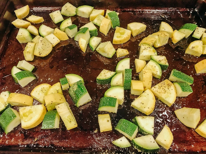 A cookie sheet filled with oven baked zucchini and squash.