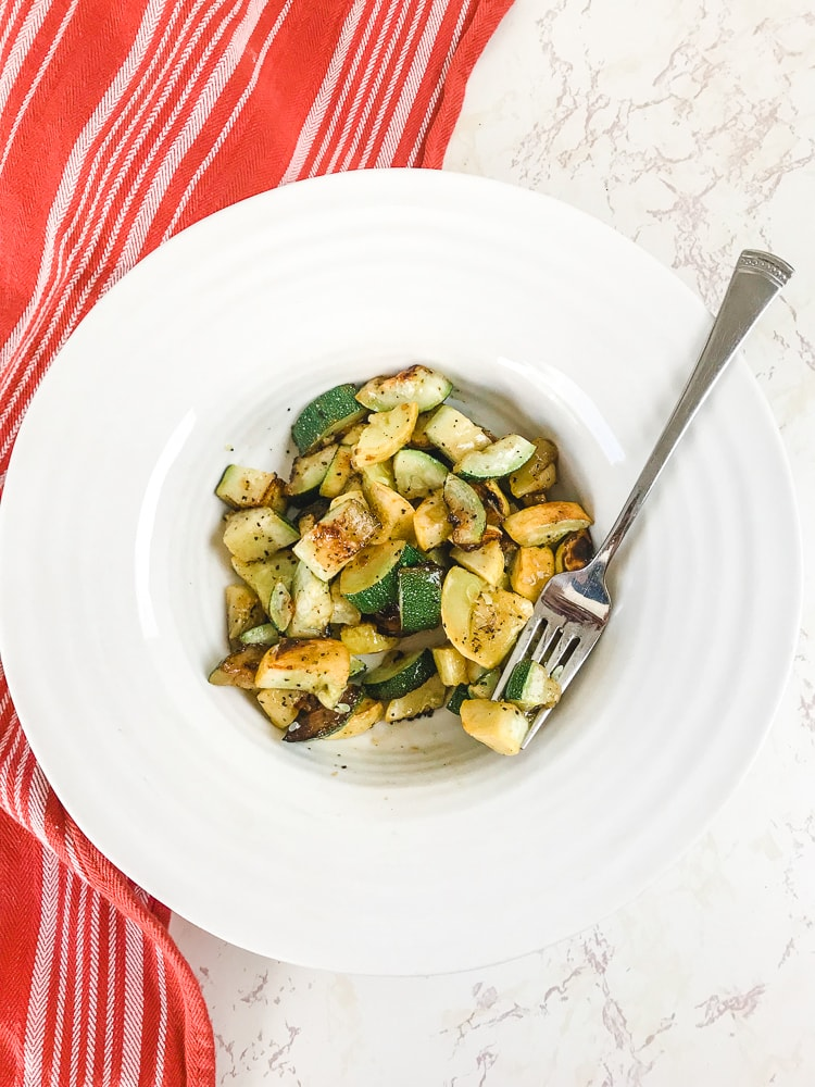 A fork holding a bite of roasted squash and zucchini over a white bowl.