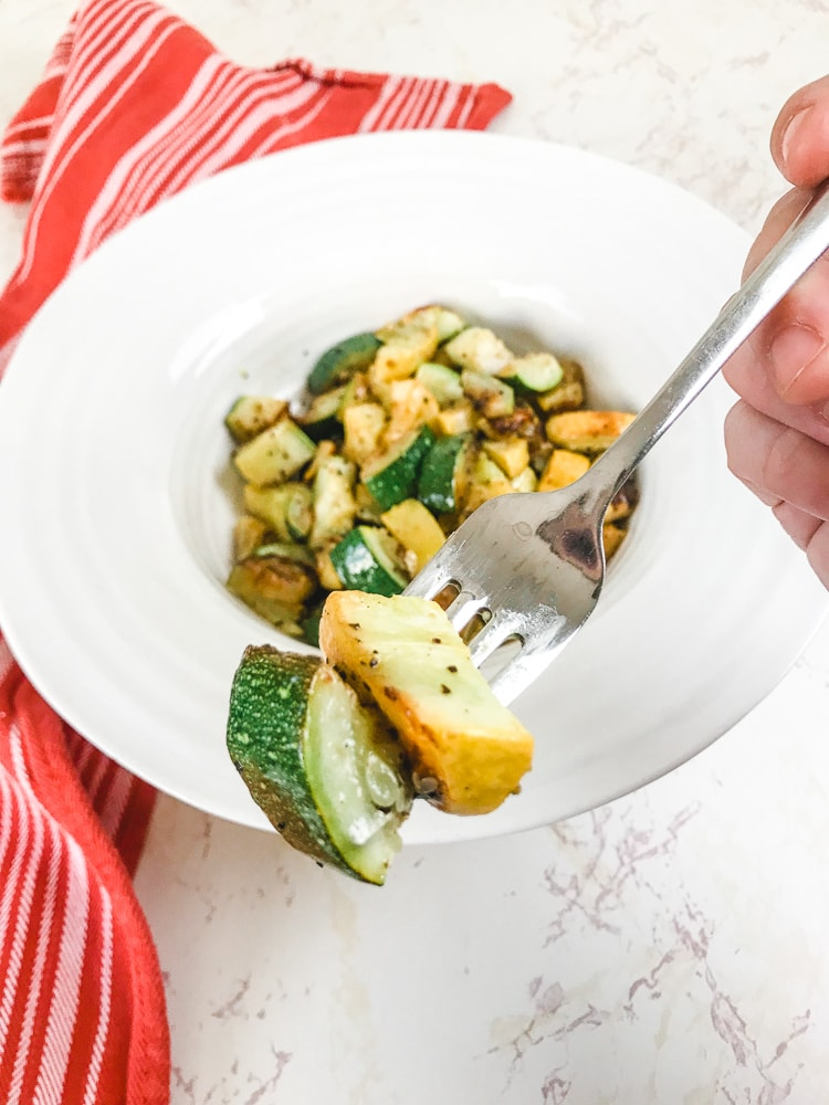 Close up of a bite of roasted zucchini and summer squash.
