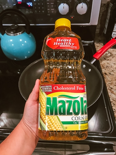 A hand holding a bottle of Mazola Corn Oil in front of a stove.
