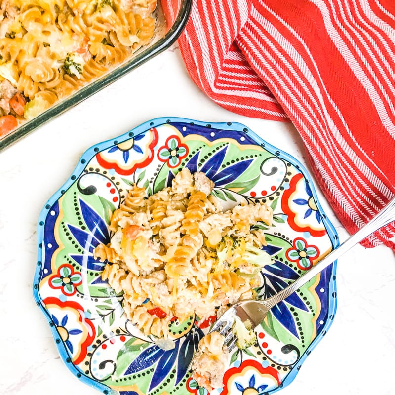 A colorful plate with a serving of turkey noodle casserole next to a red striped dish towel.