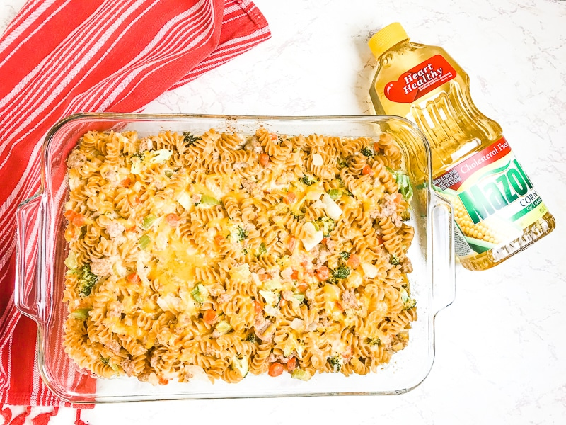 Baked turkey noodle casserole in a glass casserole dish next to a bottle of Mazola Corn Oil.