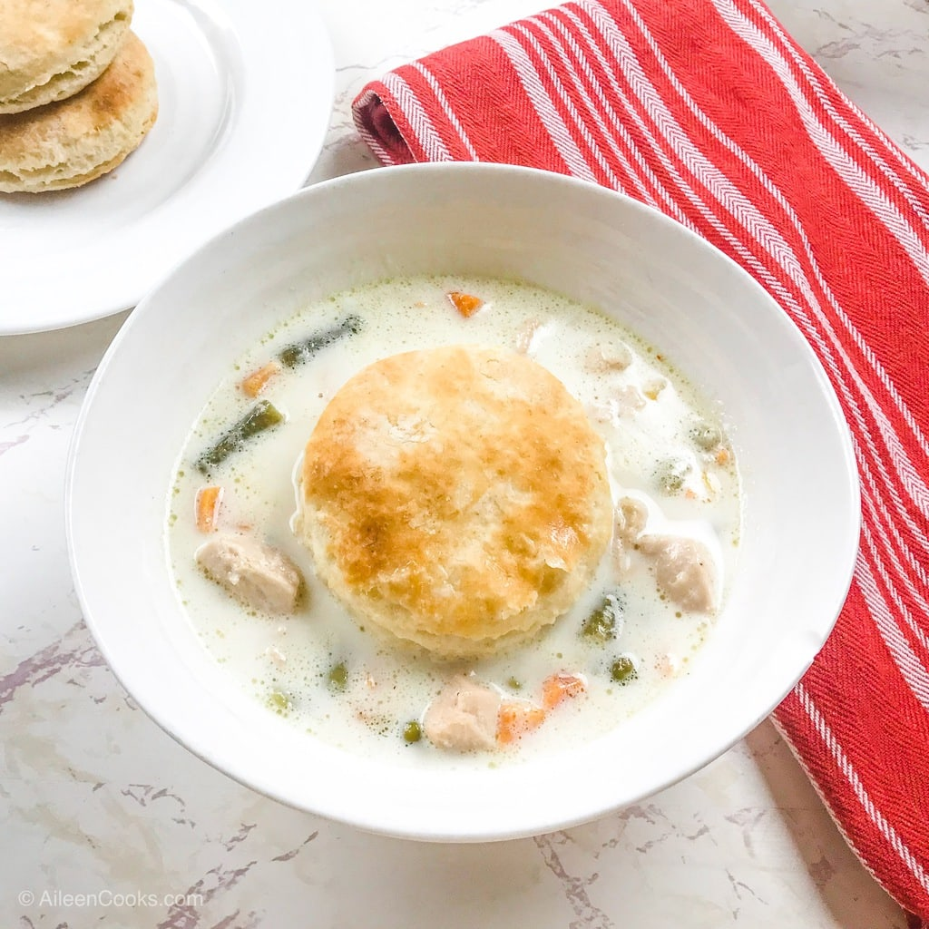 A bowl of chicken soup topped with a homemade flaky biscuit.