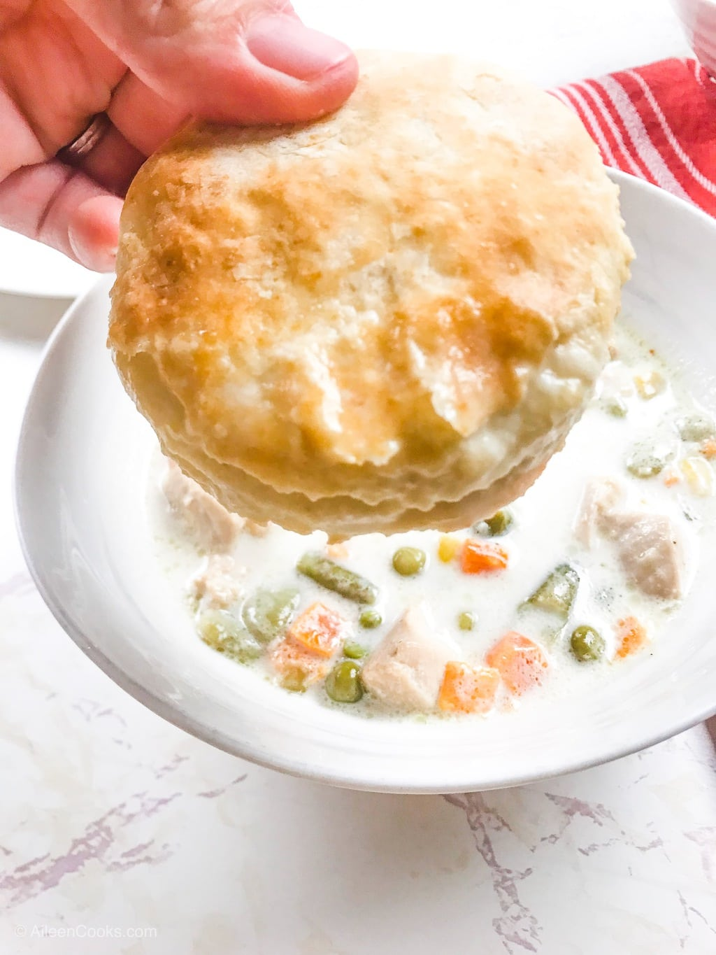 A hand holding up a biscuit that was just dunked in instant pot chicken pot pie soup.