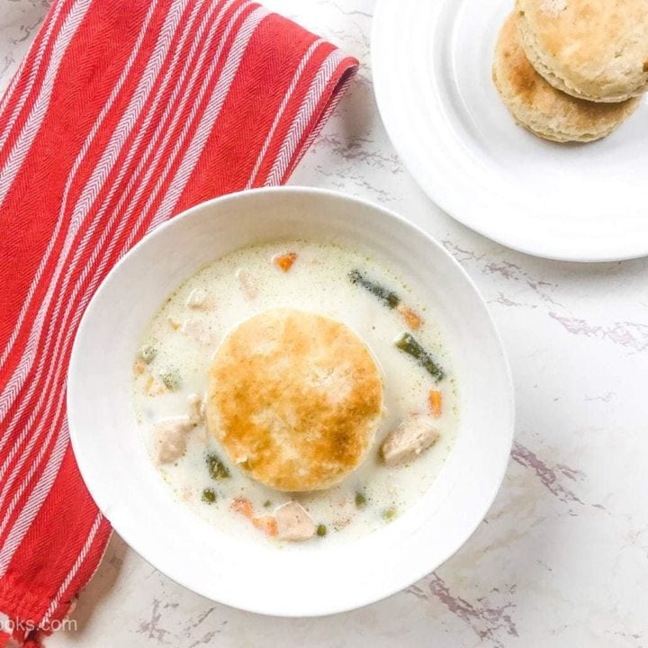 A white bowl filled with instant pot chicken pot pie soup and topped with a biscuit next to a red striped towel.