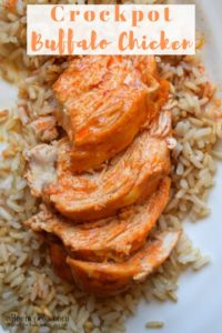 Four slices of crockpot buffalo chicken on top of a bed of brown rice.