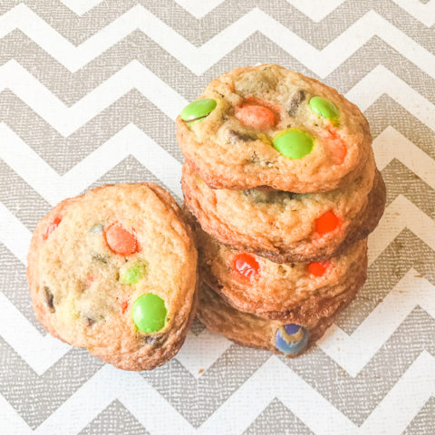 A stack of halloween cookies made with chocolate chips and orange and green M&Ms.