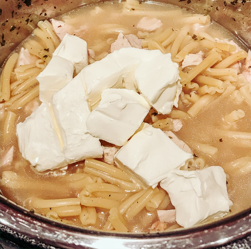 Cooked chicken and pasta with cubed cream cheese on top.