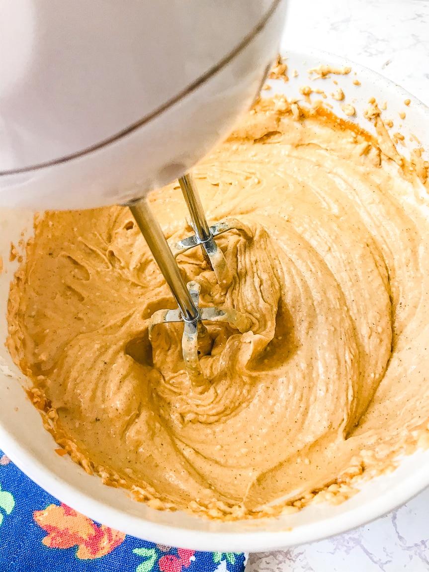 An electric mixer whisking up a batch of pumpkin pie dip.