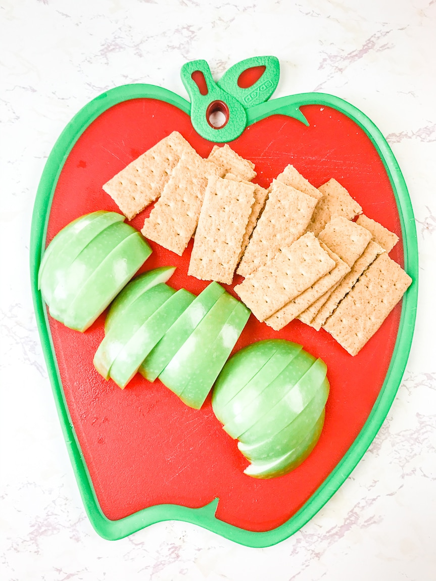 An apple shaped cutting board with sliced Granny Smith apples and a pile of graham crackers.