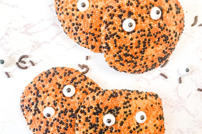 Four spooky halloween cookies surrounded by loose black sprinkles and candy eyes.