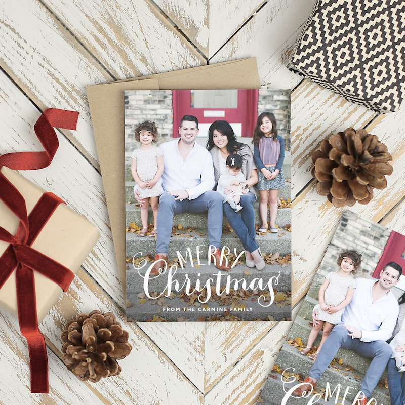 """A holiday card featuring a family and the words """"Merry Christmas""""."""