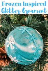 A blue frozen inspired ornament hanging from a tree.