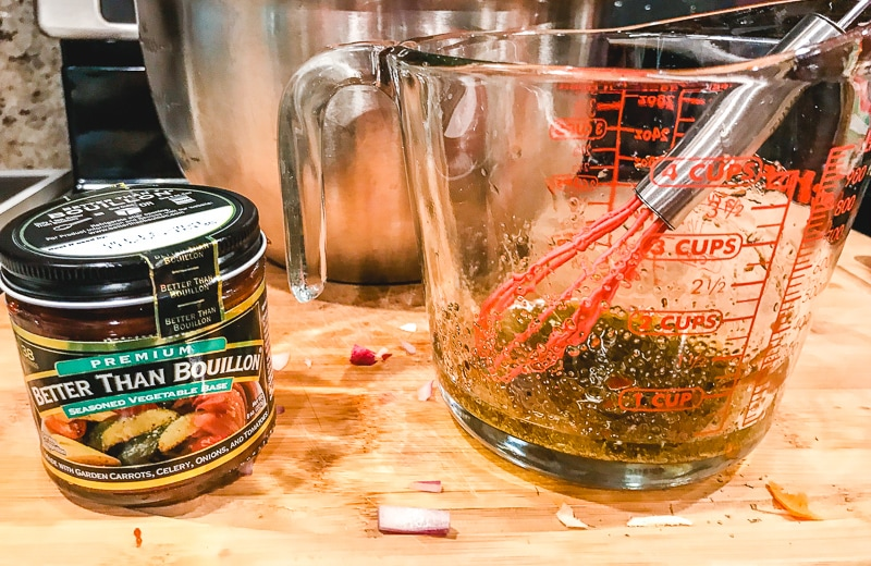 Olive oil mixture in glass measuring dish next to jar of Better Than Bouillon.