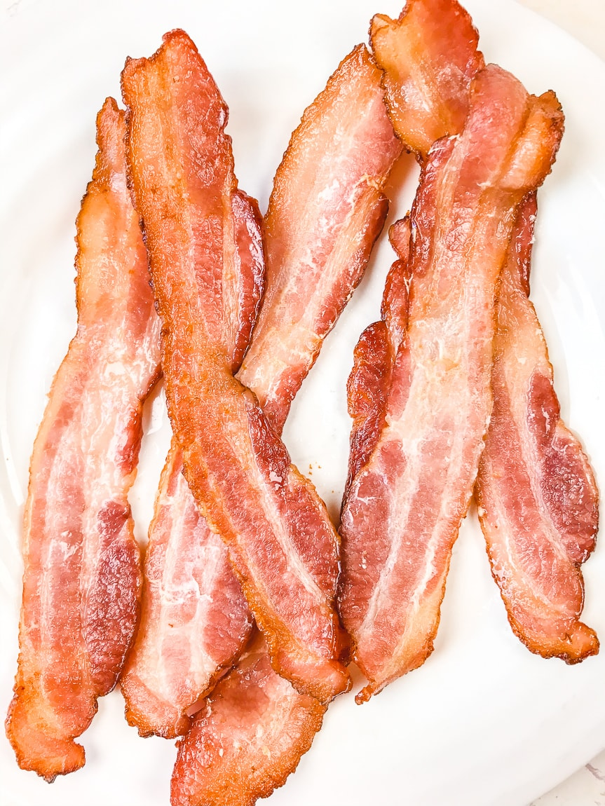 A white plate stacked with crispy air fryer bacon.