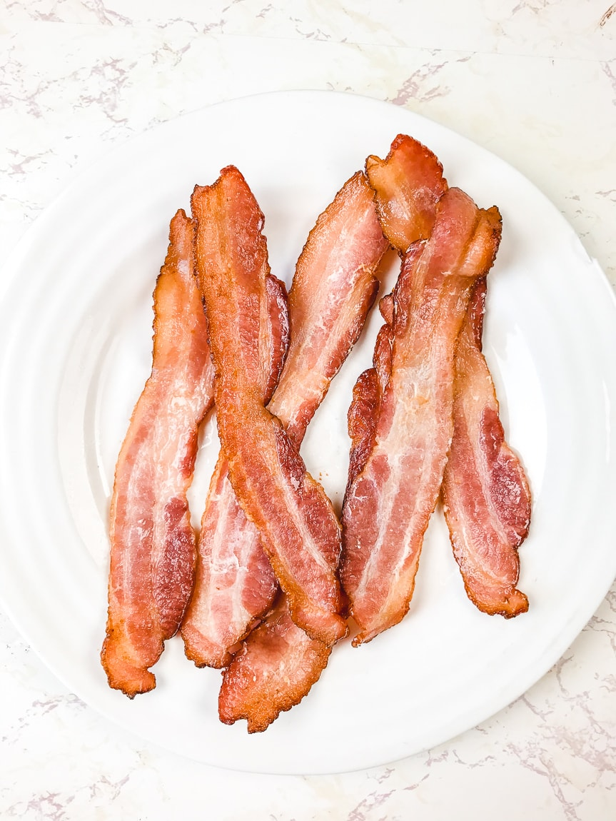 A white plate on a white counter filled with air fryer bacon.