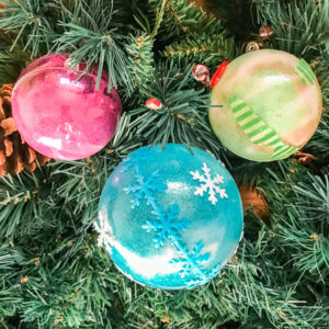 Three DIY glitter ornaments hanging on a tree.