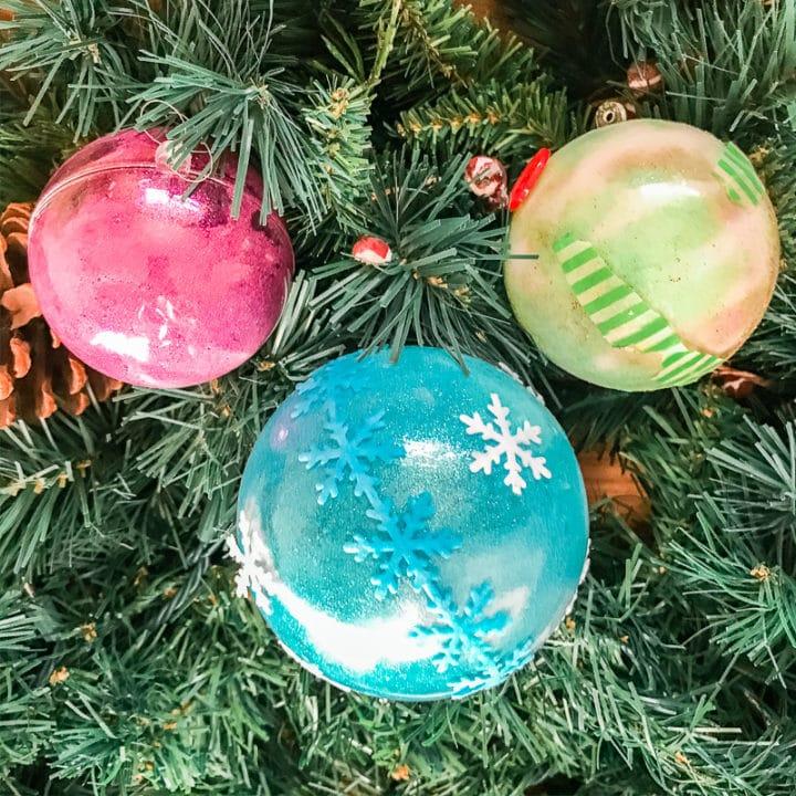Three DIY glitter ornaments hanging on a tree.