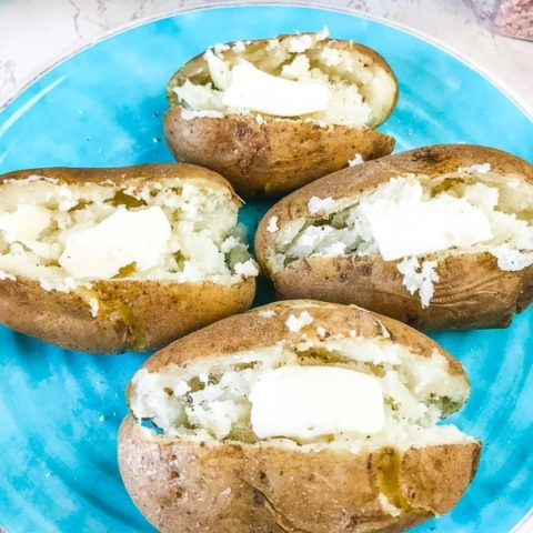 Overhead shot of instant pot baked potatoes slathered with butter.