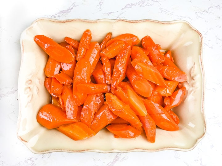 A cream colored serving dish filled with instant pot carrots.