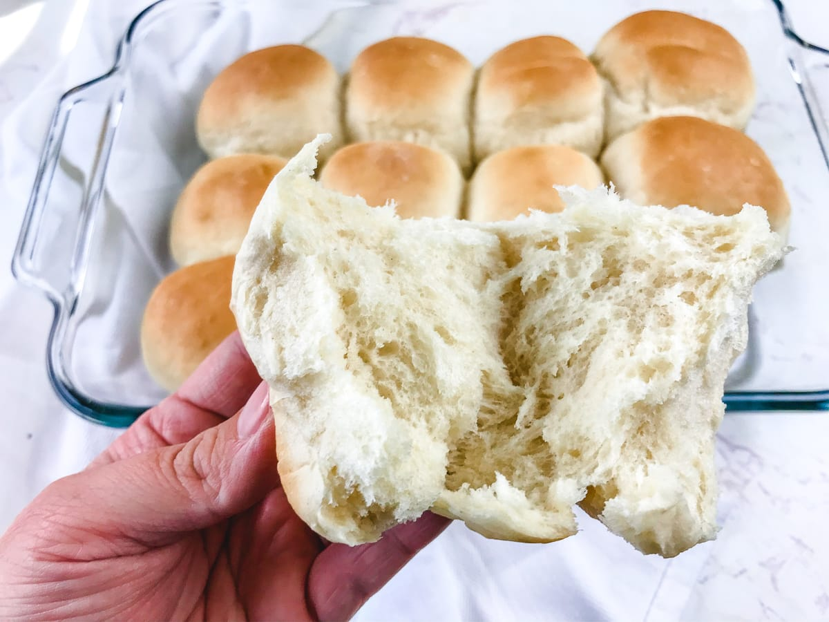 A Parker house roll split in the middle to show the soft center.
