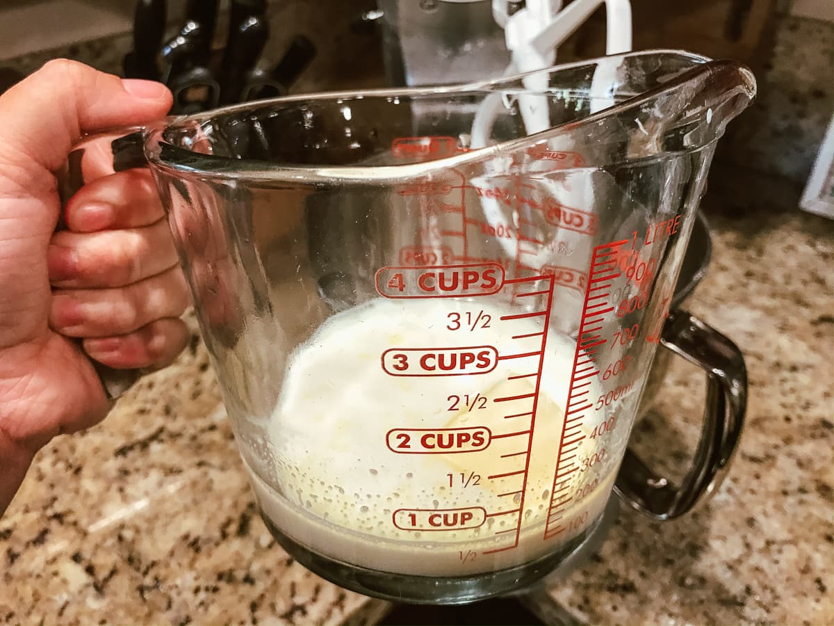 A glass measuring cup of warm milk, water, and butter.