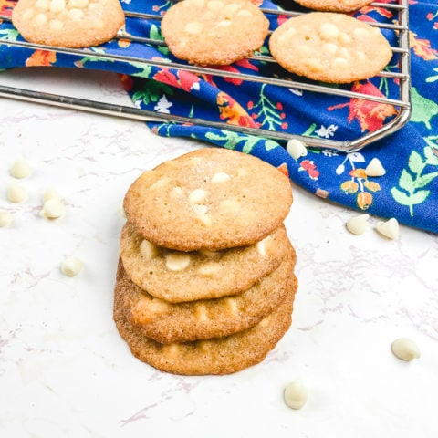 A cooling rack of cookies next to a stack of salted caramel cookies.