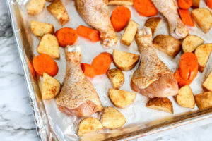 The corner of a sheet pan filled with chicken drumsticks and potatoes.