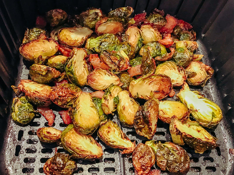 Blackened Brussels sprouts and bacon inside air fryer.