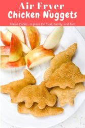 "A plate of Dino chicken nuggets and apples with words ""air fryer chicken nuggets"" in red."