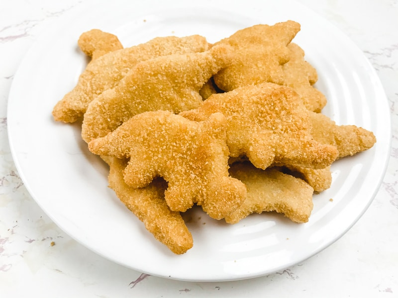 White plate filled with air fried frozen Dino shaped chicken nuggets.