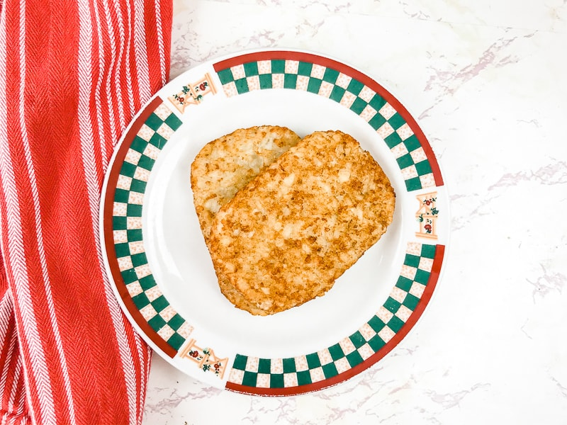 An apple printed plate with two air fried hashbrowns stacked on top of the plate.