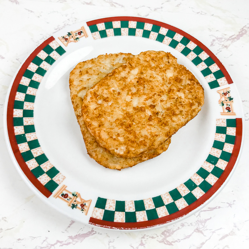 A red and green patterned plate with two hash brown patties.