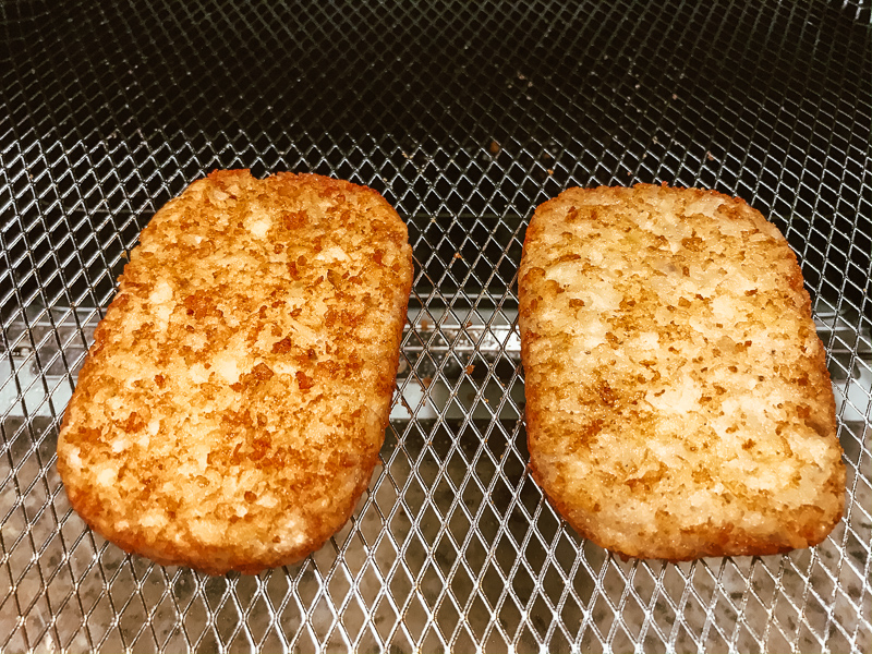 Two frozen hash brown patties inside air fryer.