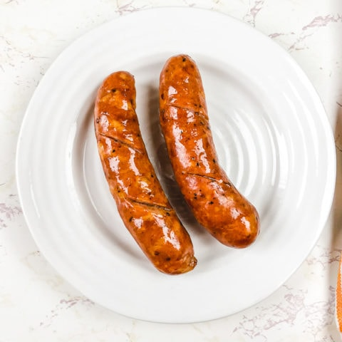 A white plate with two air fried sausage.