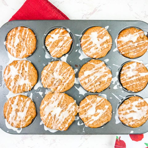 A muffin tin filled with cinnamon apple muffins next to an apple printed towel.