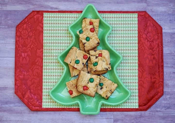 A red and green placemat with a green tree dish holding Christmas bar cookies.