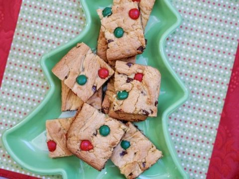 A tree shaped dish filled with Christmas cookie bars.