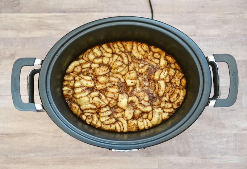 Fully cooked crock pot cinnamon roll casserole still inside of slow cooker.