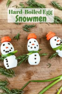 "A photo of three egg snowman snacks and the words ""hard boiled egg snowmen"""